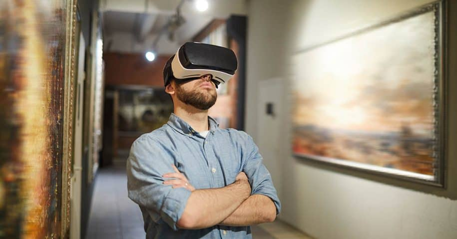Waist up portrait of modern man wearing VR headset during virtual tour in art gallery or museum